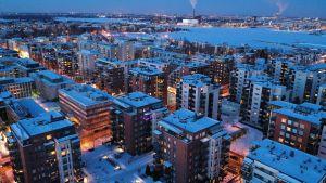 Vy över Drumsö i Helsingfors, i bakgrunden syns Gräsviken. En massa bostadshus med tända lampor en vinterkväll.