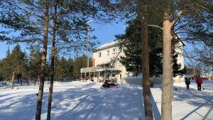 En 50-talsbyggnad i i en tallskog med snö i omgivningen.