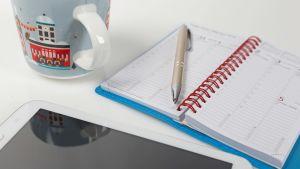 Pöydällä on kahvikuppi, iPad ja paperinen kalenteri, jonka päällä on kynä.