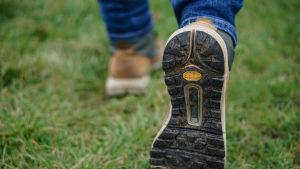 Kengänpohja näkyy, kun henkilö kävelee nurmikolla.