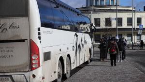 Ihmisiä nousee bussiin Turun linja-autoasemalla