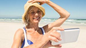 Äldre leende kvinna står på solig strand och ser på sin telefon