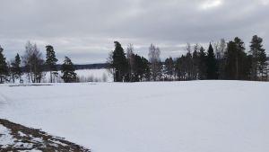 Snöigt landskap med frusen sjö i bakgrunden.