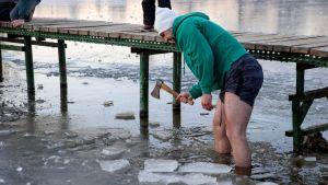 Mies seisoo jääsohjossa ja hakkaa kirveellä jäätä.