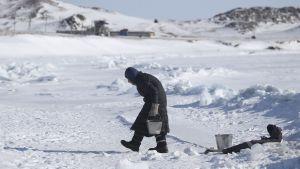 Kyyryselkäinen vanhus kävelee metalliämpärin kanssa lumisessa maisemassa.