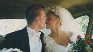 Huntuun ja morsiuspukuun pukeutunut Helena Ahti-Hallberg suutelee tuoreen aviomiehensä Ericin kanssa hääauton takapenkillä.