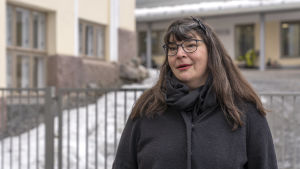 Pia Tyyskä står framför ett metallstaket.