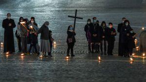 Barn och unga beskådar Via Crucis-ceremonin som leddes av påven på långfredagen 2.4.2021
