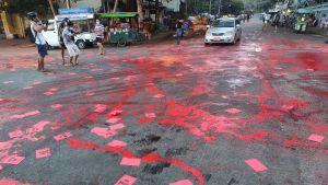 En gata har målats med röd målfärg i protest mot militärkuppen.