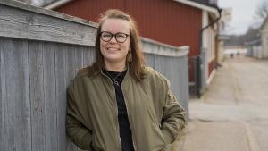En kvinna står lutad mot ett staket och tittar in i kameran.