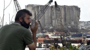 En man blickar ut mot hamnen i Beirut som ännu inte har återbyggs sedan explosionen i augusti i fjol.