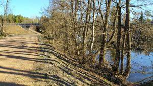 Sandväg, en älv till höger täckt av träd, längst fram skymtar en motorvägsbro i betong.