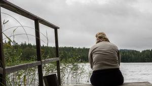 En kvinna sitter på ändan av en brygga en mulen dag.