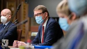 Matti Vanhanen sitter med munskydd på vid ett bord, i förgrunden en suddig Centerordförande Annika Saarikko.
