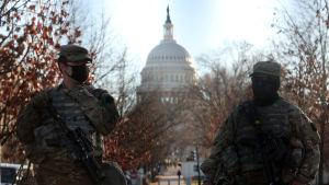 Två kamouflageklädda militärer med munskydd spanar med kongressens vita kupol i bakgrunden.