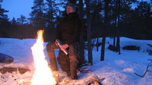 Man sitter i skogen vid elden.