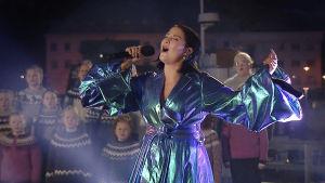 Molly Sandén uppträder på Oscarsgalan 2021, på Island. I bakgrunden står en barnkör och sjunger med.