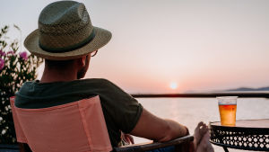 Man fotad bakifrån, sitter utomhus och ser mot himlen, har en öl bredvid sig på ett bord
