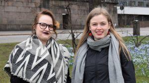 Två unga kvinnor ler mot kameran.