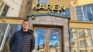 En man står utanför Kåren i Åbo. Bilden taget snett nerifrån.