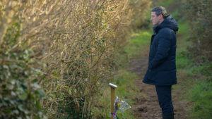 Luke Evans tuijottaa muistolaattaa.