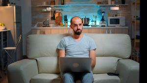 Man sitter i soffa med dator i famnen och ser fundersam ut