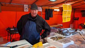 Fiskhandlare Tuomas Kajasola står bakom disken på sitt försäljningsstånd på Salutorget.