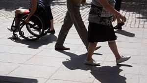 En rullstolsburen person syns bland människor som är ute och går.