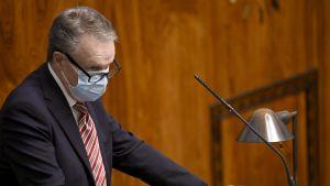 Ilkka Kanerva står i en talarstol i riksdagen. Han har munskydd på sig.