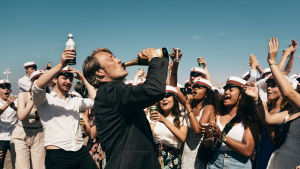 Martin (Mads Mikkelsen) dricker direkt ur en champangeflaska medan unga studenter jublar runtom honom.