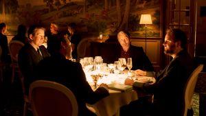 Tommy (Thomas Bo Larsen), Peter (Lars Ranthe), Martin (Mads Mikkelsen) och Nikolaj (Magnus Millang) sitter vid ett bord i en fin restaurang.