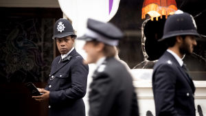 Leroy Logan (John Boyega) bobbyn uniformussa. Taustalla rikottu ikkuna, etualalla muita poliiseja.
