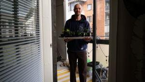 Mies seisoo parvekkeella taimia sylissään.