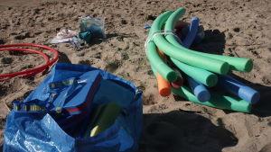 Vattenleksaker på en sandstrand.