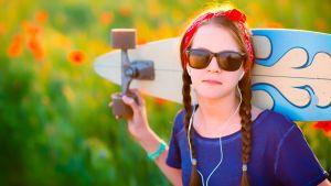 Tyttö aurinkolaseissa pitää isoa longboard-rullalautaa olkapäillään värikkään pellon laidalla.