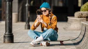 Pipopäinen tyttö istuu skeittilaudan päällä ja tutkii puhelintaan.