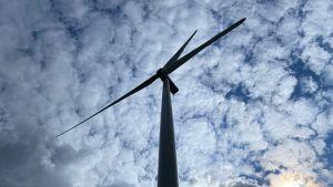 en bild av en vindmölla taget från marken så man ser rotorbladen och den molniga himlen