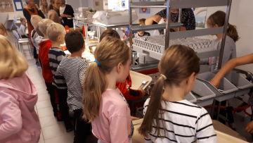 Barn i kö till skollunchen i en matsal.