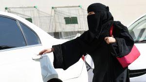 Saudiarabisk kvinna vid bil.
