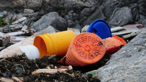 Plasthinkar som ligger och skräpar på en strand.