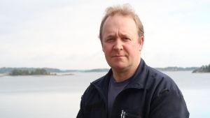 Peter Fihlman i mörk fleece, havet i bakgrunden