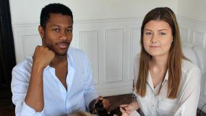 En man och en kvinna sitter vid ett bord. De tittar in i kameran. I händerna håller de löshår. De är make up-artister och hårstylister.