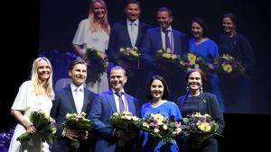 Aura Salla, Antti Häkkänen, Petteri Orpo, Sanni Grahn-Laasonen och Mari-Leena Talvitie står med blommor på scen på Samlingspartiets partikongress.