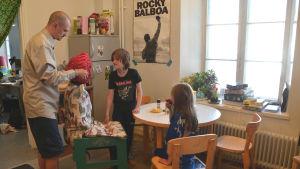 Längst till vänster står en man och drar på en luva på en kvinna som sitter vid ett matbord, utklädd till stol. Till höger om henne står en pojke och ser på medan en flicka sitter på en stol vid matbordet och äter ett äppel.