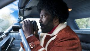 Ron Stallworth (John David Washington) sitter i en bil och spanar med sin kikare.