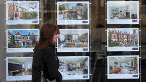 Kvinna som går framför reklam på hus som är till salu.