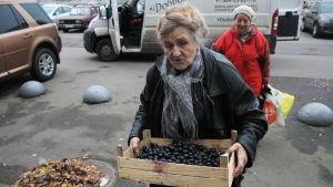 En äldre dam bär vindruvor och annan mat till en behövande