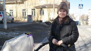 Elisabeth Glatz står ute på gatan med en barnvagn