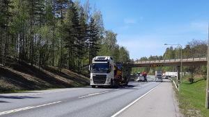 Långtradare och bilar kör på riksväg 25 i Ekenäs under en bro.