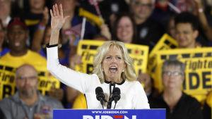 Jill Biden sträcker upp handen när hon står i en talarstol och pratar till Joe Biden anhängare.